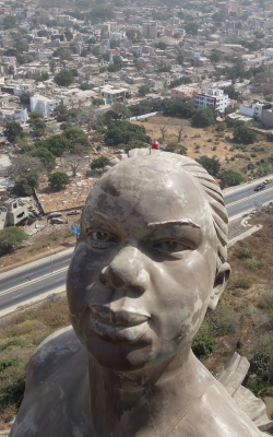 Picture of the African Renaissance statue in Dakar. In the background the city crowds of houses.